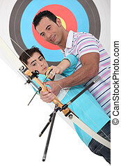 father and son practicing archery together
