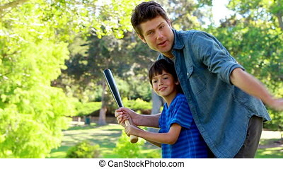 Father and son practicing baseball in a park