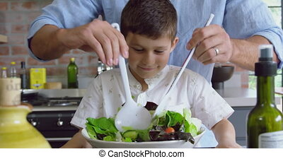 Father and son preparing fruit salad on a table in kitchen at home 4k
