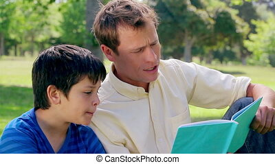 Father and son reading a book aloud