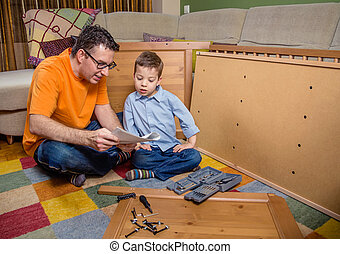 Father and son reading instructions to assemble furniture -...
