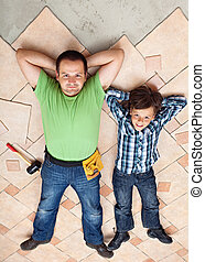Father and son resting on unfinished floor tiles surface