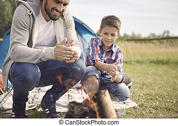 Father and son rubbing hands over the campfire