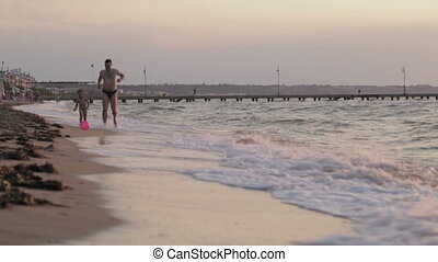 Father and son running along the beach with ball
