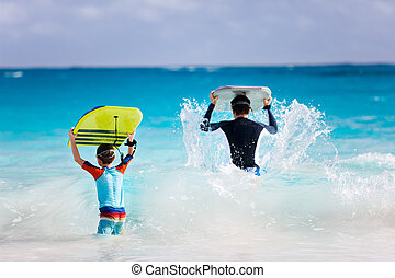 Father and son running with boogie boards