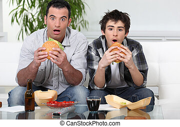 Father and son sat on the sofa eating burgers
