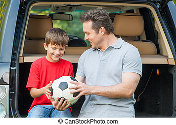 Father and son sit near car with opened boot and going to...