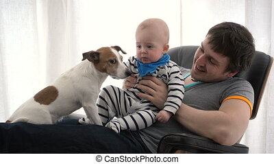 Father and son sitting in a armchair with a dog Jack Russell...
