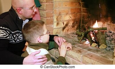 Father and son sitting near fireplace
