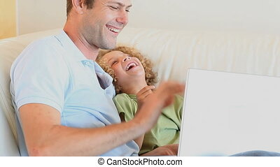 Father and son sitting on a sofa while using a laptop
