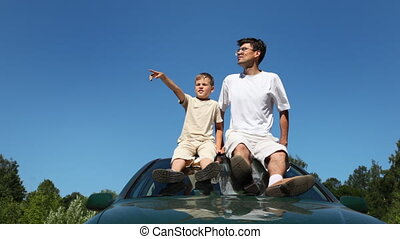 father and son sitting on roof of car, boy shows his hand at something, part1