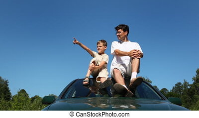 father and son sitting on roof of car, boy shows his hand at something, then man hugs him, part1