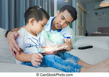 Father And Son Sitting On Sofa Using Digital Tablet.