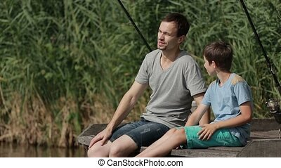 Father and son sitting on the pier and fishing - Happy...