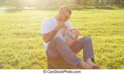 Father and son sitting together on the grass in summer evening sunset