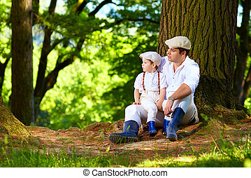 father and son sitting under an old tree in forest