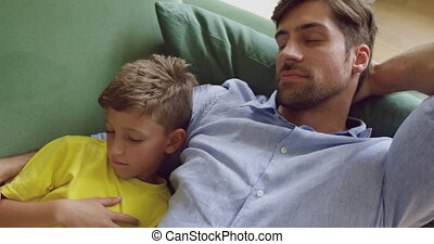 Father and son sleeping together on sofa at home 4k