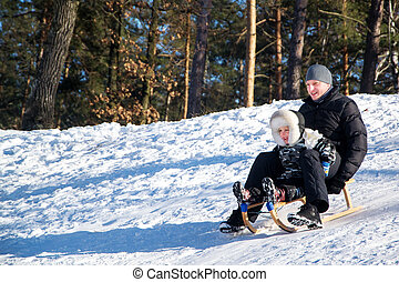 Father and son sliding in the snow.
