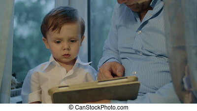 Father and son spending leisure time with touch pad - Little...