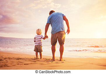 Father and son standing on the sea shore holding hands at...