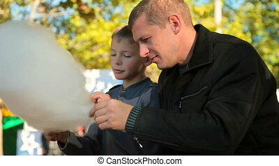 father and son enjoying cotton candy at a fair