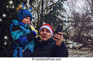 Father and son take a selfie near the Christmas tree