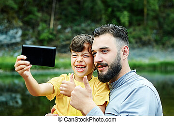Father and son take selfies in nature.