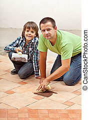 Father and son testing the joint material color on ceramic tiles floor - focus on boy