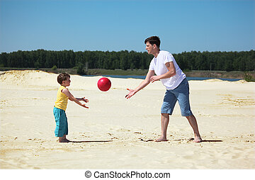 father and son throw each other ball on sand