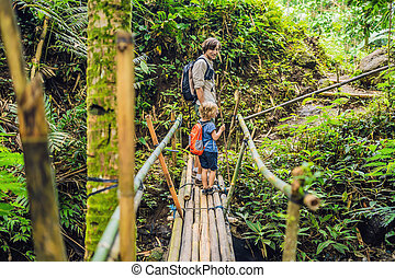 Father and son travelers on the suspension bridge in Bali. Traveling with children concept.