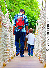 father and son traveling by suspension bridge