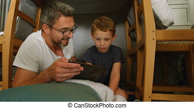 Father and son using digital tablet in living room 4k -...