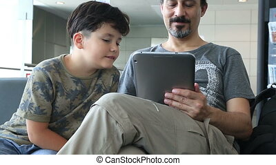 Father and son using i pad at the a