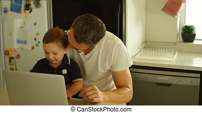 Father and son using laptop in kitchen 4k - Father and son...