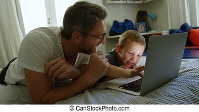 Father and son using laptop on bed 4k