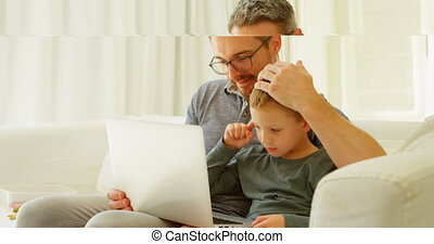 Father and son using laptop on sofa 4k