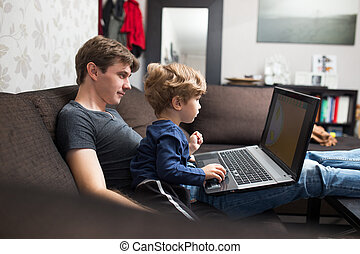 Father and son using laptop together on sofa at home