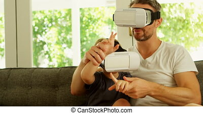 Father and son using virtual reality headset on sofa 4k -...