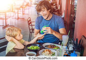 Father and son using wash hand sanitizer gel before eating in a cafe with sunlight