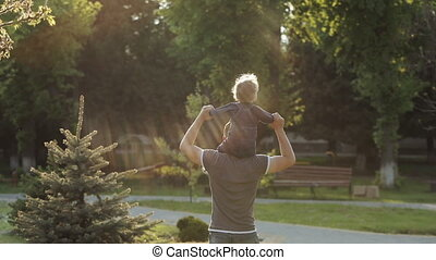 Father and son walking in park at sunset. Two year old kid is sitting on the parent's shoulders. Happy family concept.