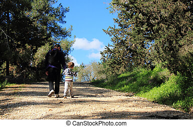 father and son walking in spring forest