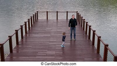 Father and son walking on bridge - Parent and child go to...