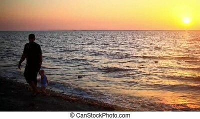father and son walking on the beach at sea And beautiful sunset
