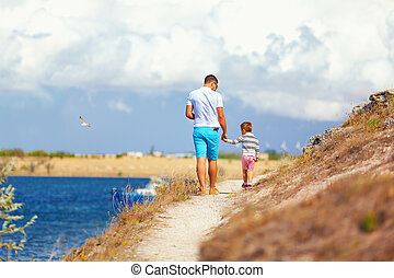 father and son walking on the cliff, seaside