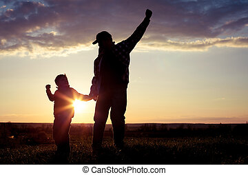 Father and son walking on the field at the sunset time.