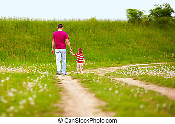 father and son walking rural footpath