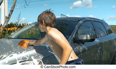 Father and son wash the car together. Near his country house.