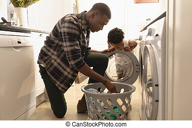 Father and son washing clothes in washing machine - African...