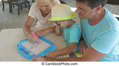 Father and son watch mother is painting pet on magnet board...