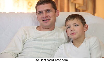 Father and son watching television together sitting on the couch in the living room